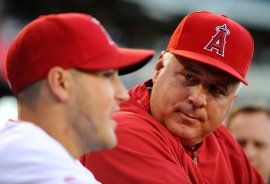 Manager Mike Scioscia listens to Officer Alex Collins in the dugout. Photo by Matt Brown/Angels Baseball LP