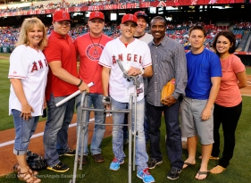 Alex Collins, a peace officer who was wounded in the Christopher Dorner case, is surrounded by Tony Phillips and family after throwing the ceremonial first pitch. Photo by Matt Brown/Angels Baseball LP