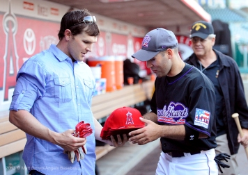 Brendan Harris gives Angels hats to a player in the Purple Heart baseball game on Armed Forces Day at Angel Stadium. Photo by Matt Brown/Angels Baseball LP