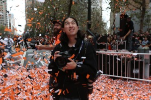 SAN FRANCISCO - OCTOBER 31:  Team photographer Andy Kuno of the San Francisco Giants works on Market Street during the World Series parade on October 31, 2012 in San Francisco, California. (Photo by Brad Mangin)